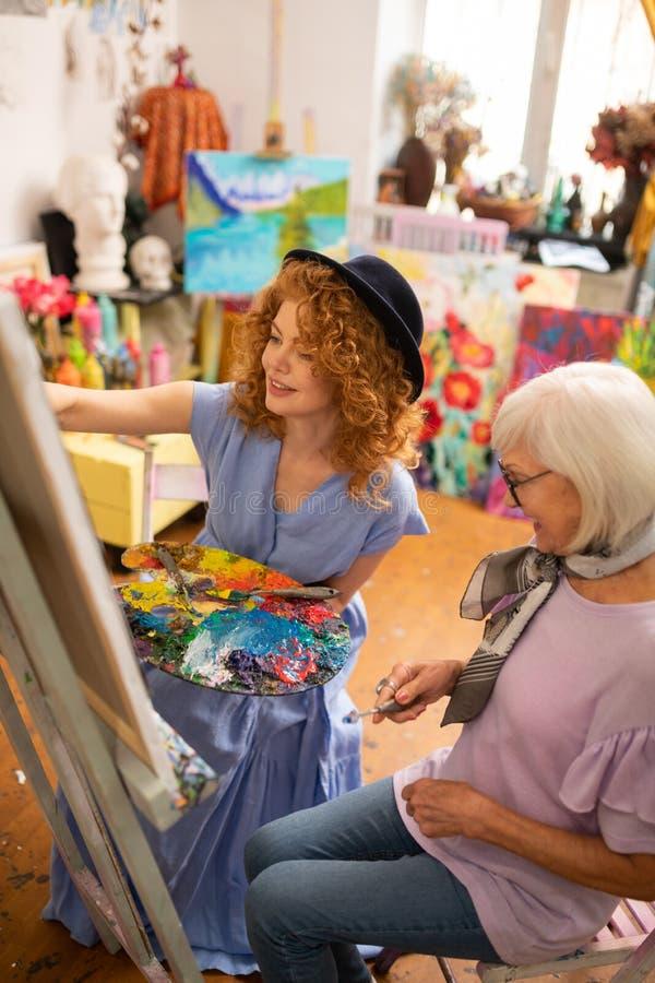 年轻在老师附近的艺术家佩带的礼服和帽子绘画 免版税库存照片