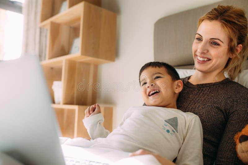 年轻在膝上型计算机的家庭观看的动画片 库存照片