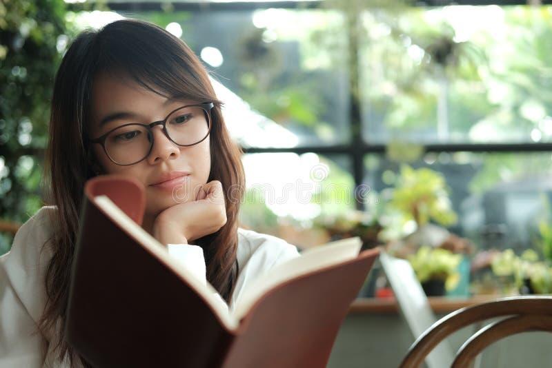 年轻坐在图书馆和readi的学生妇女佩带的玻璃 免版税图库摄影
