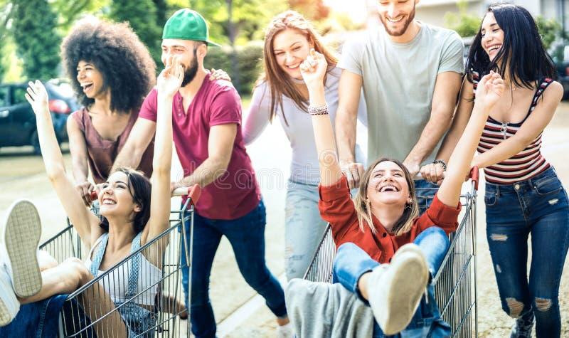年轻多种族人民获得乐趣与手推车-分享时间的Millenial朋友一起与台车在商业购物中心 免版税图库摄影