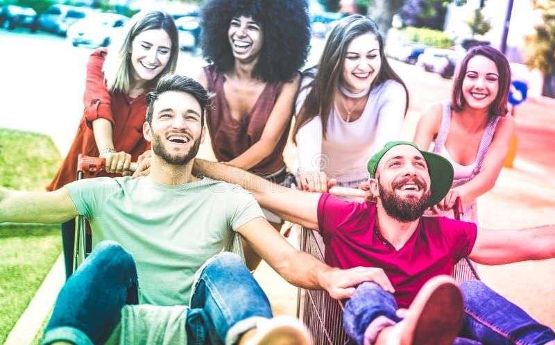年轻多种族朋友获得乐趣与手推车-分享时间的千福年的人民一起与台车在商业购物中心 库存照片