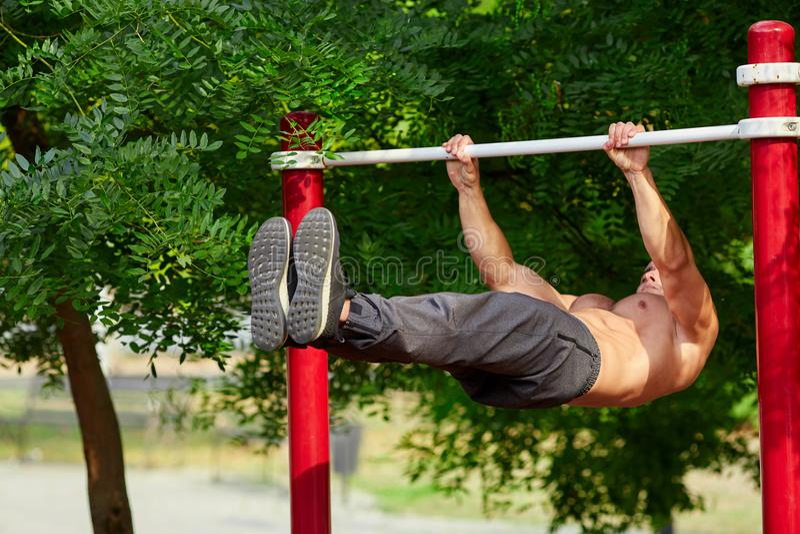 年轻大力士在夏天做在一架单杠的引体向上在一个运动场在城市 库存图片