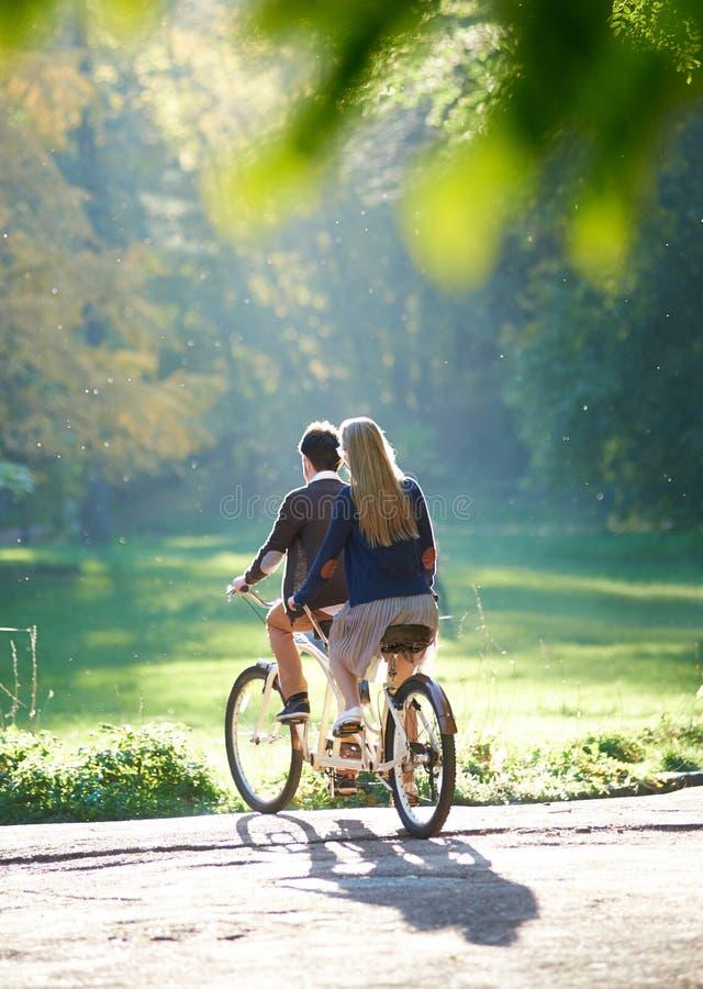 年轻夫妇、英俊的男人和可爱的妇女纵排自行车的在晴朗的夏天公园或森林 免版税库存照片