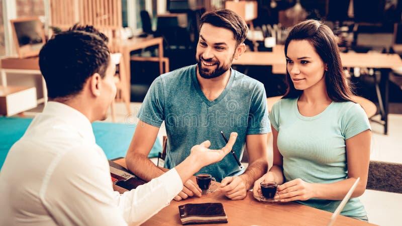 年轻夫妇与家具卖主协商 库存照片
