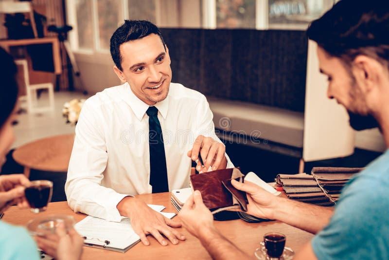 年轻夫妇与家具卖主协商 免版税图库摄影