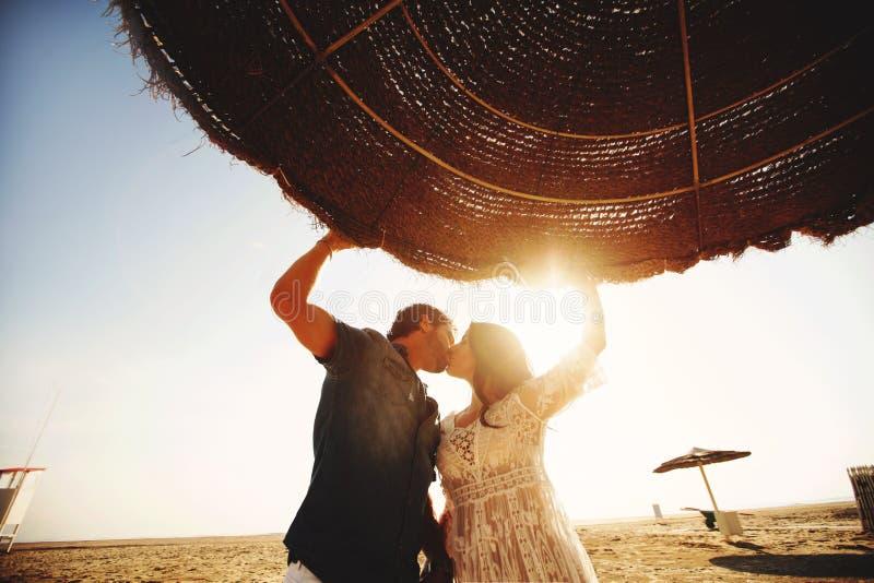 年轻夫妇举行手和亲吻在伞下,在海滩和晴朗的天空的背景 意大利,里米尼 免版税库存图片