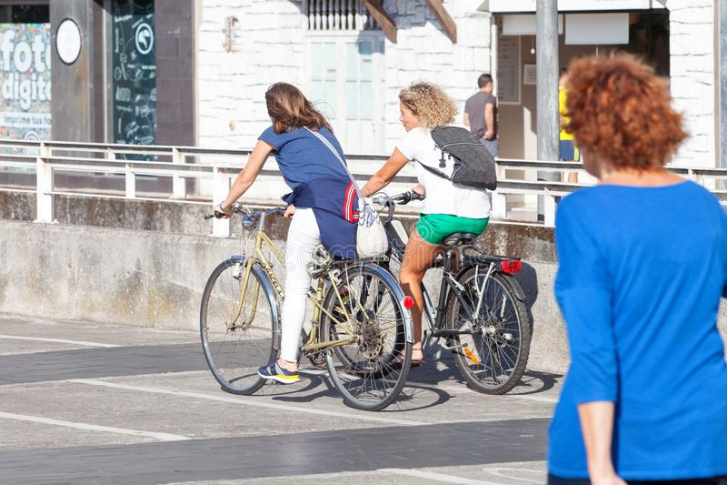年轻夫妇乘坐的自行车在城市 免版税图库摄影