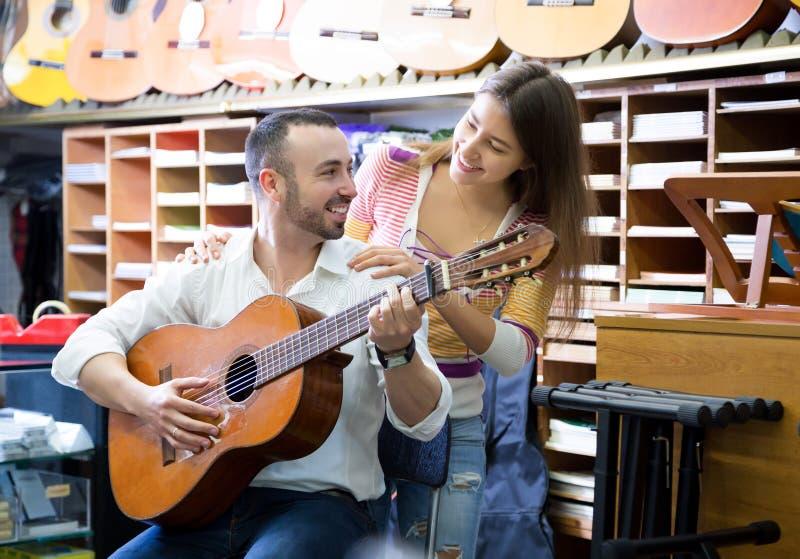年轻夫妇买的吉他在商店 库存图片
