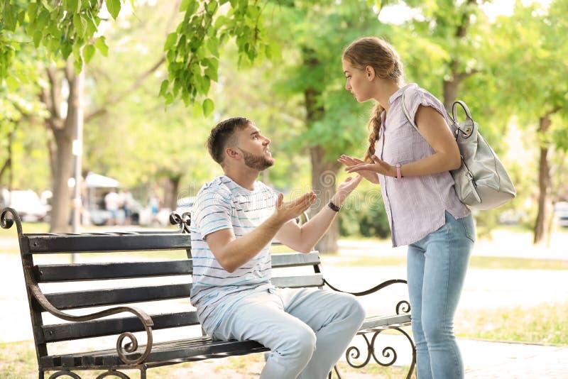 年轻夫妇争论在公园 在关系的问题 库存照片