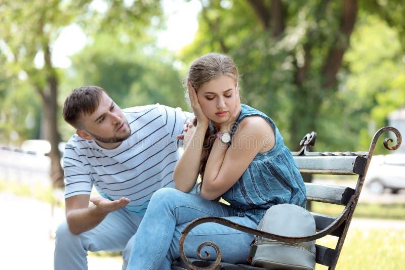 年轻夫妇争论在长凳在公园 在关系的问题 免版税库存图片