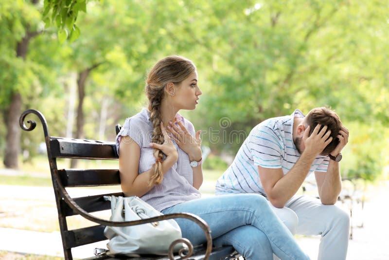 年轻夫妇争论在长凳在公园 在关系的问题 库存图片