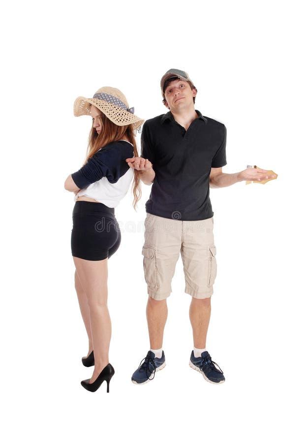年轻夫妇争论,站立无能为力 库存照片