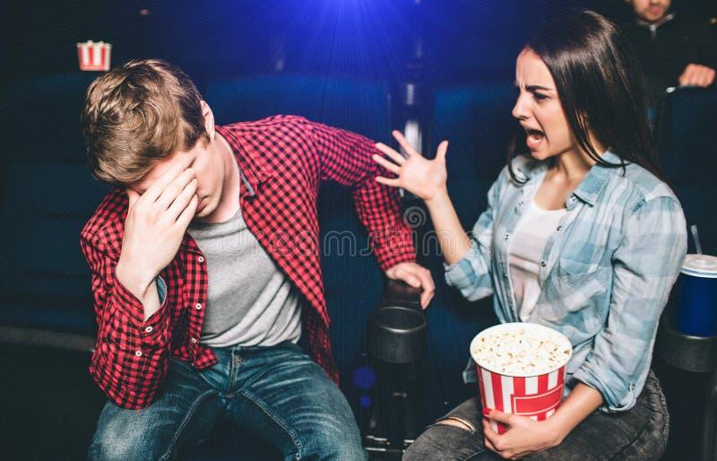 年轻夫妇争论 女孩是叫喊和叫喊对她的男朋友 他对丑闻和盖他的面孔是疲乏 库存照片