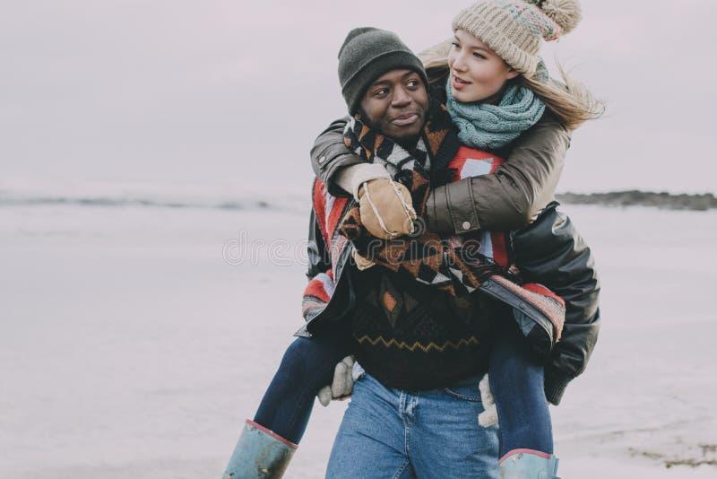 年轻夫妇享用冬天海滩 免版税库存图片