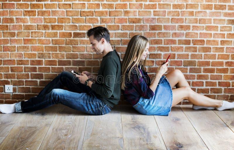 年轻夫妇使上瘾对智能手机和社会媒介 免版税库存照片