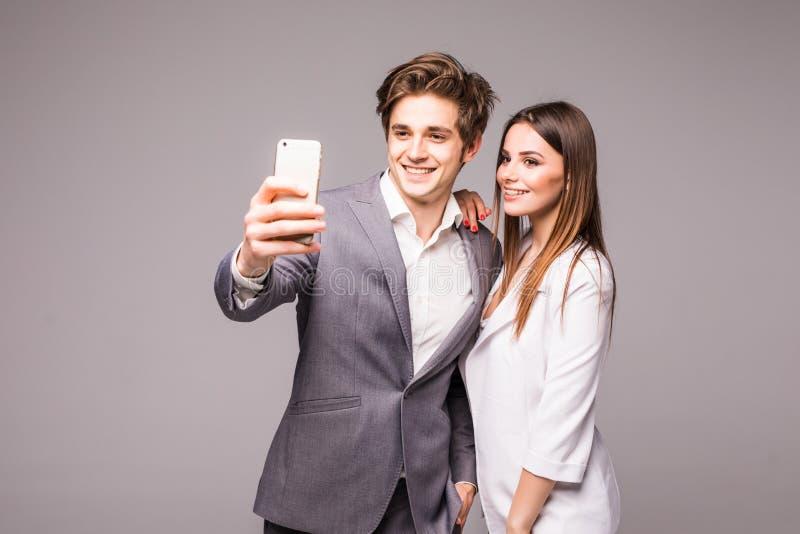 年轻夫妇使用巧妙的电话并且微笑着,当常设时采取在灰色背景的selfie 免版税库存图片