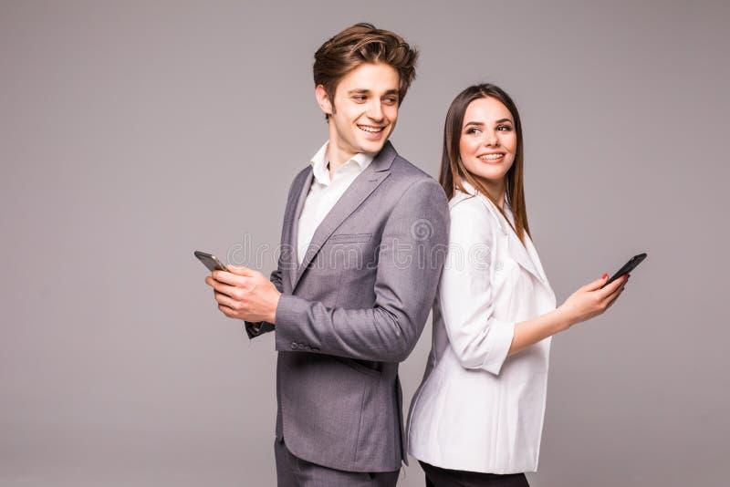 年轻夫妇使用巧妙的电话并且微笑着,当紧接站立在灰色背景时 互相看 免版税库存图片