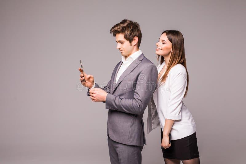年轻夫妇使用巧妙的电话并且微笑着,当紧接站立在灰色背景时 妇女看看人 库存图片