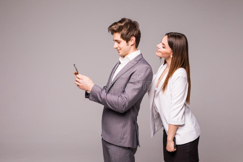 年轻夫妇使用巧妙的电话并且微笑着,当紧接站立在灰色背景时 妇女看看人 库存照片