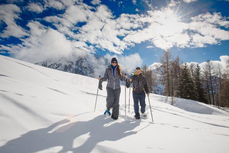 年轻夫妇做在山的雪靴远足 库存照片
