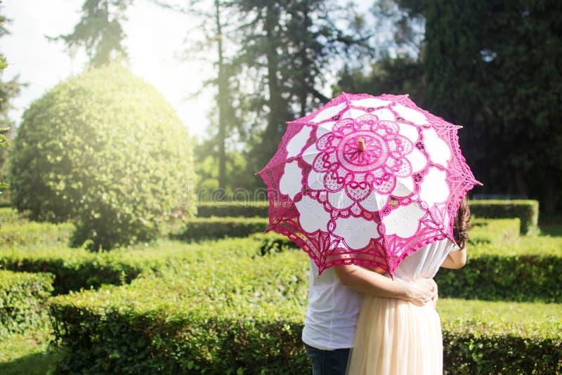 年轻夫妇剪影在伞后的在森林里 免版税库存照片