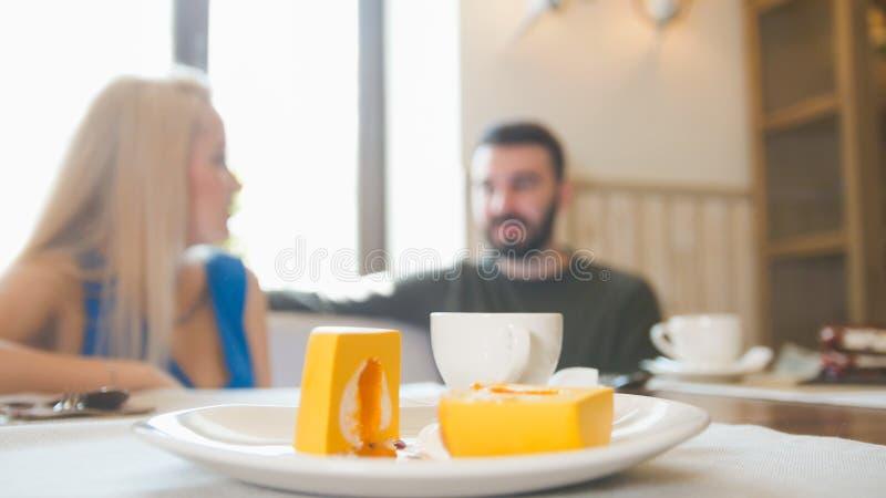 年轻夫妇吃午餐在咖啡馆女服务员通过- defocused 免版税库存图片