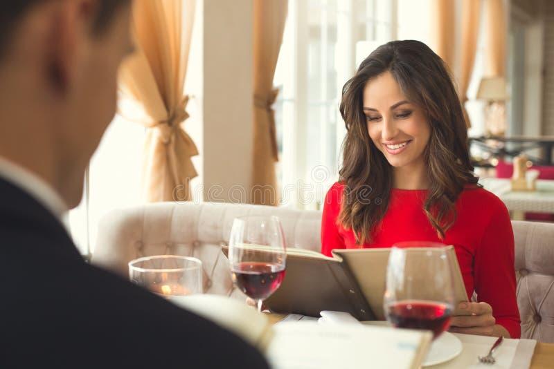 年轻夫妇吃浪漫晚餐在举行菜单选择的餐馆 免版税库存图片