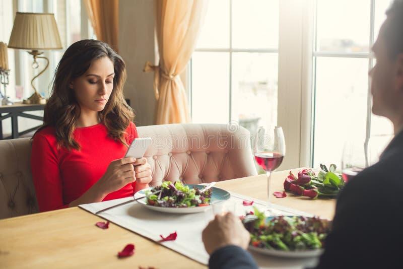 年轻夫妇吃浪漫晚餐在餐馆使用乏味的智能手机 库存图片