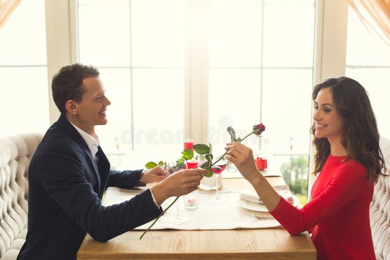 年轻夫妇吃浪漫晚餐在餐馆玫瑰色花礼物 库存图片