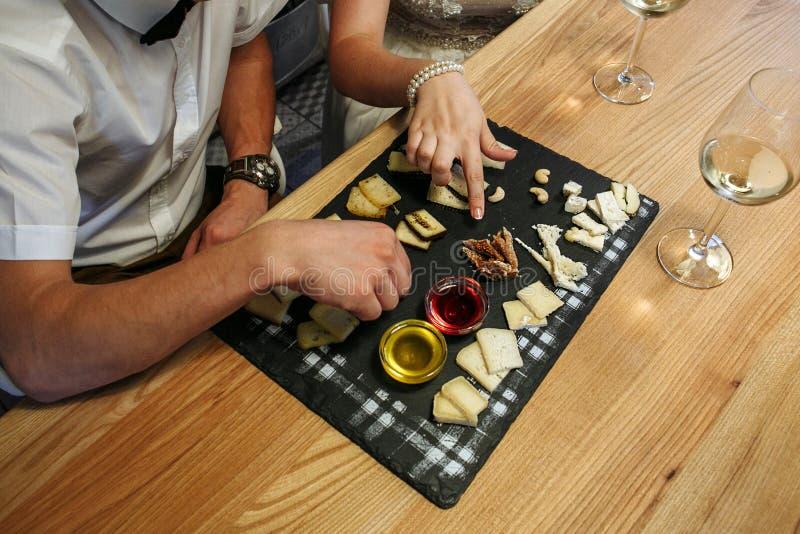 年轻夫妇品尝乳酪和白葡萄酒 图库摄影