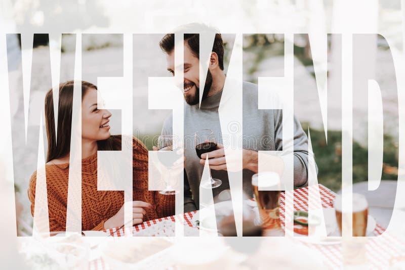 年轻夫妇喝着烤肉假期 免版税库存图片