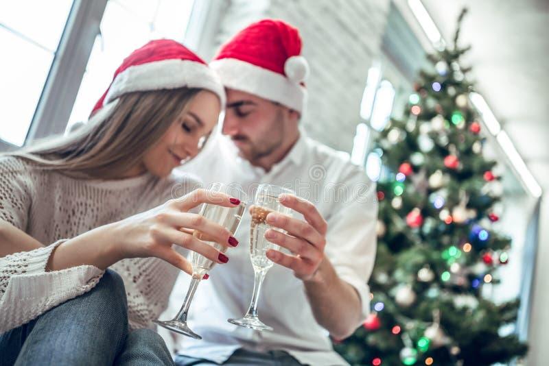 年轻夫妇喝香槟,看彼此和微笑;在Xmas树附近在家 图库摄影