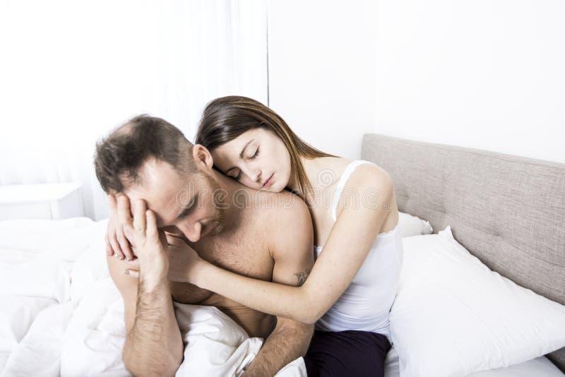 年轻夫妇在与联系问题的床上 库存图片