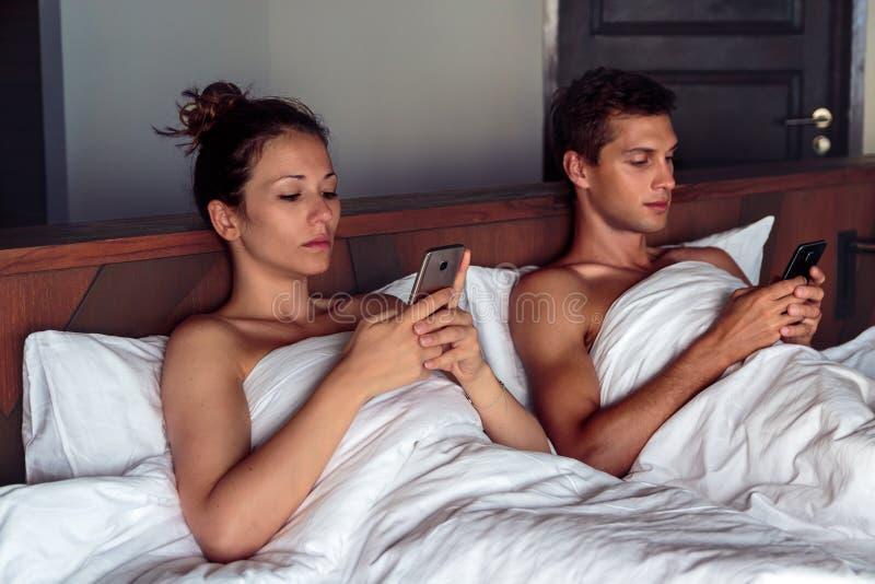 年轻夫妇在使用他们的忽略的智能手机的床上 库存图片