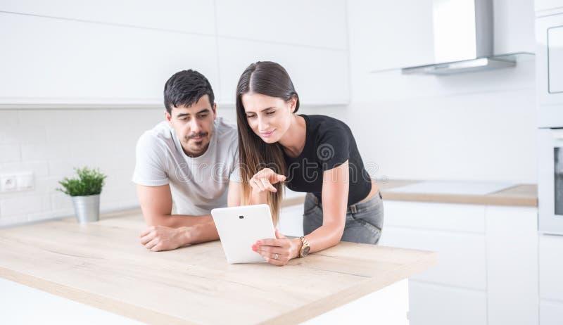 年轻夫妇在使用片剂的家庭厨房里 图库摄影