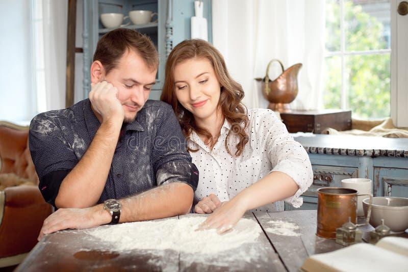 年轻夫妇在使用用面粉的厨房里 滑稽的片刻,微笑,烹调,愉快一起,记忆 免版税库存图片