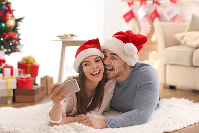 年轻夫妇在做selfie的圣诞老人帽子 免版税库存图片