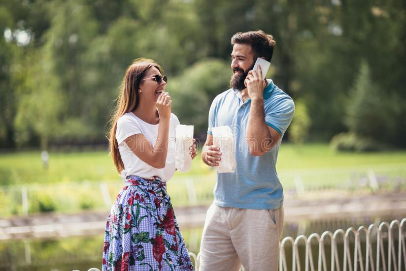 年轻夫妇在吃玉米花的公园 库存照片