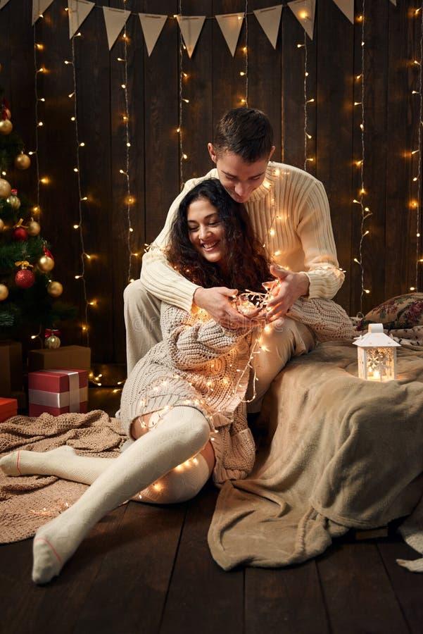 年轻夫妇在圣诞灯和装饰,穿戴在白色,在黑暗的木背景,寒假概念的杉树 免版税库存照片
