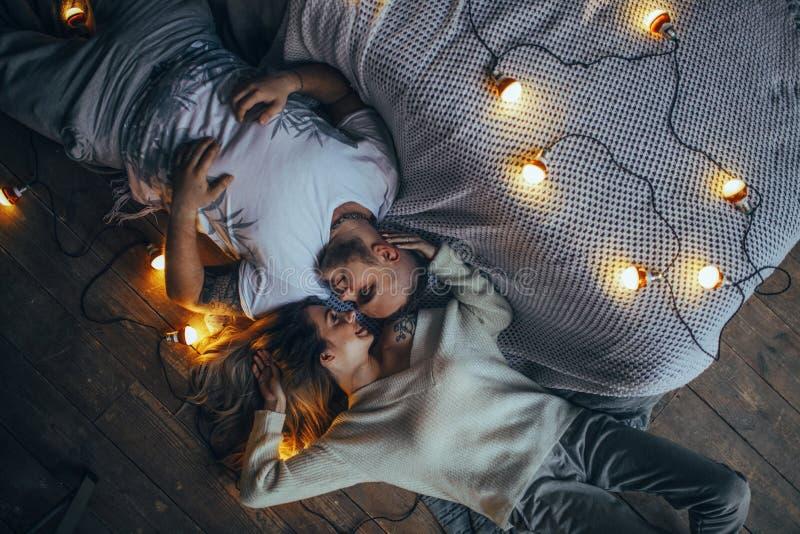 年轻夫妇在地板上在backgroun说谎,微笑着并且拥抱 库存照片