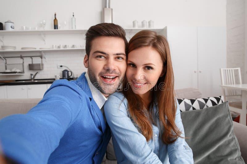 年轻夫妇在家一起过周末拍快乐selfie的照片 免版税库存照片