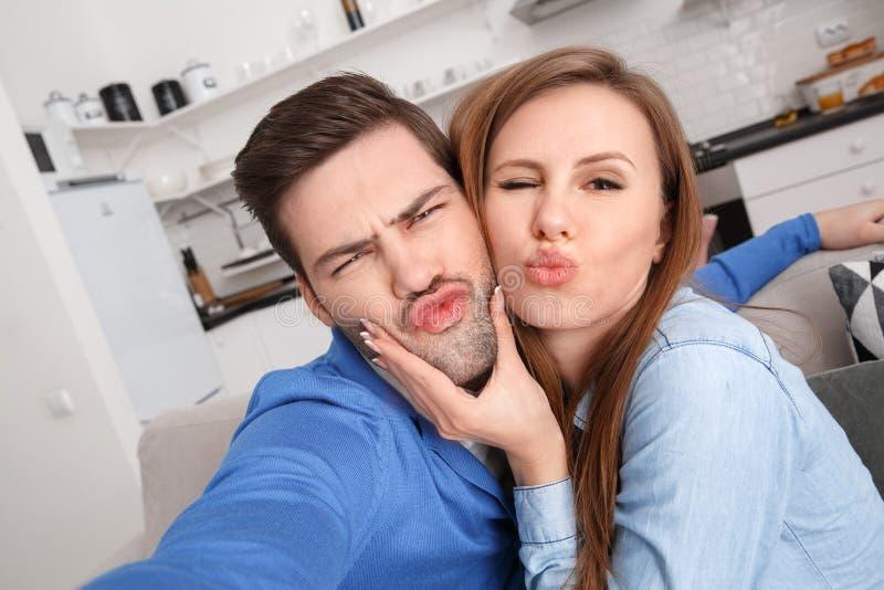 年轻夫妇在家一起过周末拍滑稽的照片 免版税库存图片