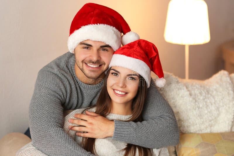 年轻夫妇在家休息圣诞老人的帽子 免版税图库摄影