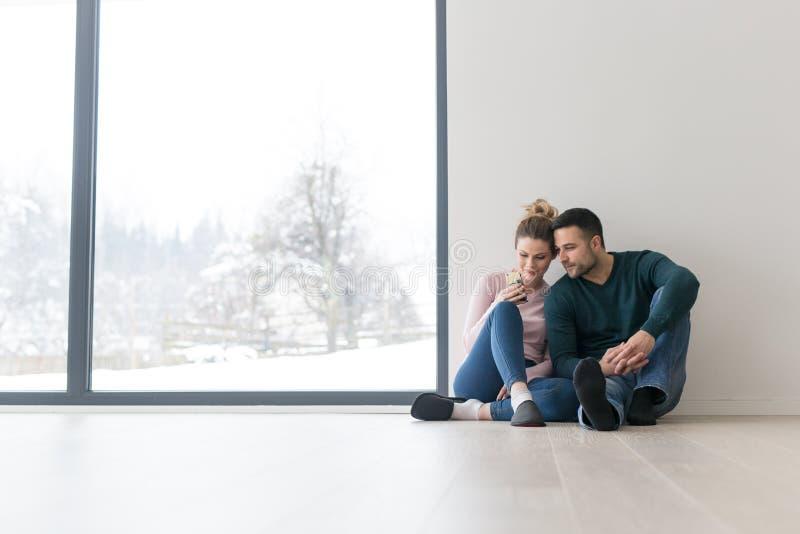 年轻夫妇在家坐地板在窗口附近 图库摄影