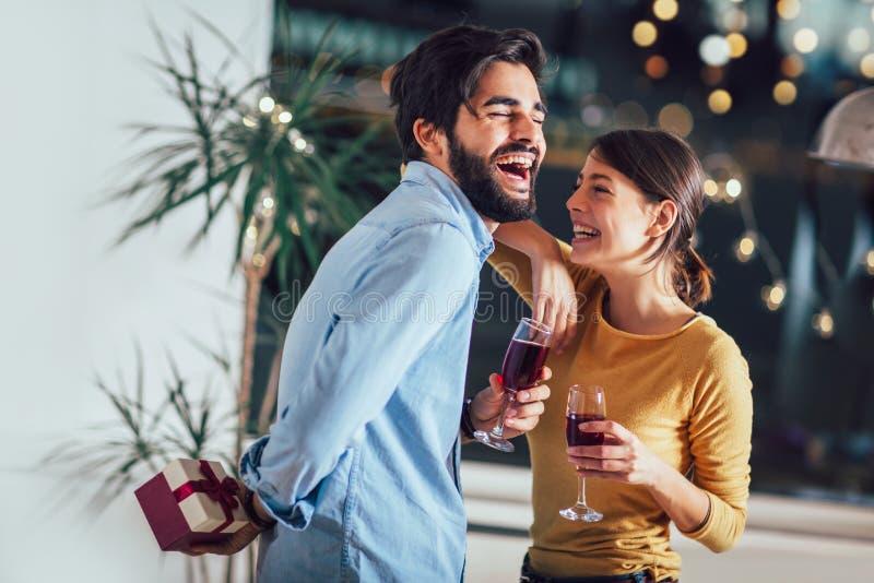 年轻夫妇在家庆祝 英俊的人给他的女朋友一个礼物盒 免版税库存照片