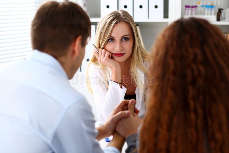 年轻夫妇在家庭医生办公室结合在一起使胳膊 免版税库存照片
