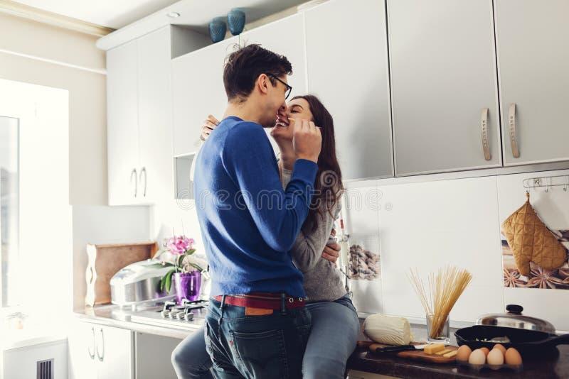 年轻夫妇在拥抱和吃乳酪的厨房里 免版税库存图片