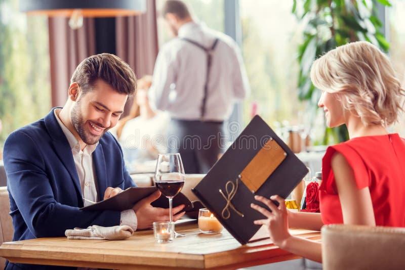 年轻夫妇在日期在坐的餐馆选择盘从快乐的菜单 免版税库存照片
