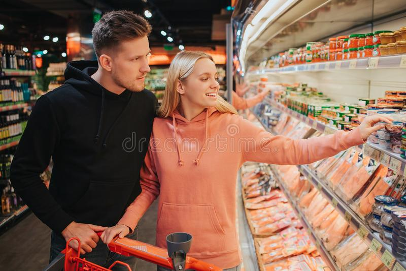 年轻夫妇在杂货店 他们一起采摘海鲜 在淡菜的年轻女人点刺激并且微笑 人立场 免版税图库摄影