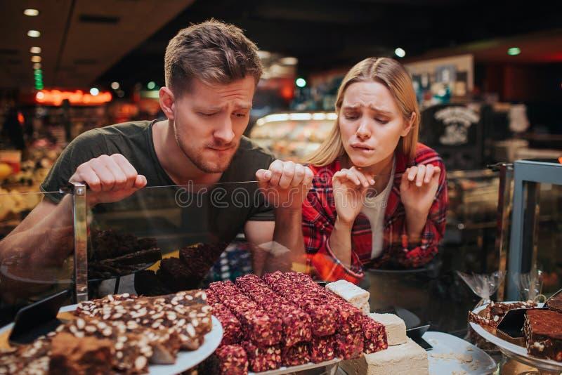 年轻夫妇在杂货店 他们看甜点以饥饿和热爱 鲜美可口甜点 免版税库存照片